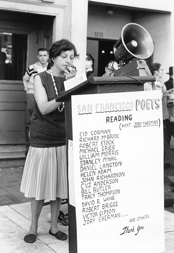 Picture ruth weiss in the 1950s speaking in public with a loud projector
