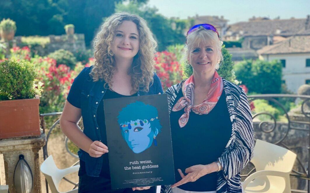 Picture of Melody and Elisabeth in Asolo Italy holding up the poster of ruth weiss the beat goddess for the premiere