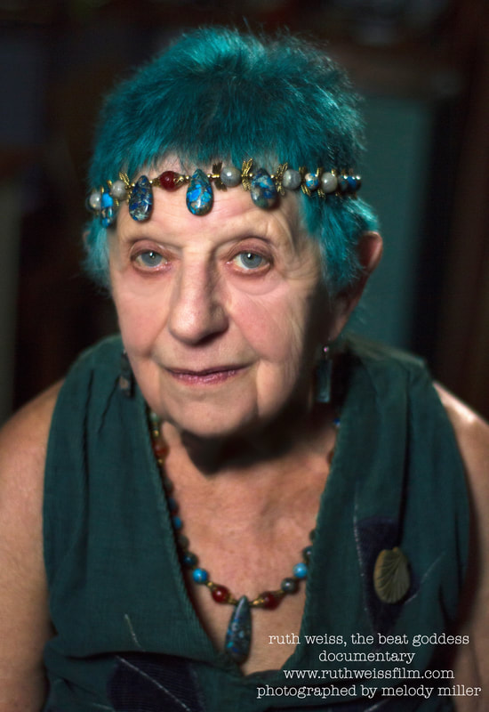 Picture of ruth weiss. she has blue hair and crystals on her head at age 91